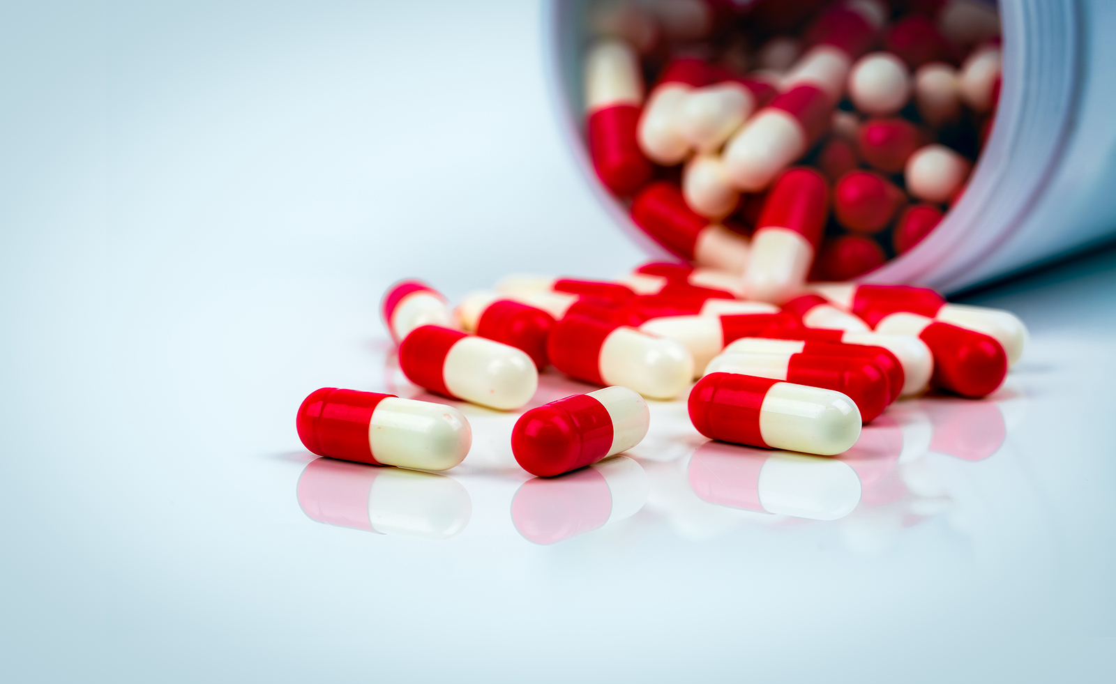 Red-white capsule pills on white table
