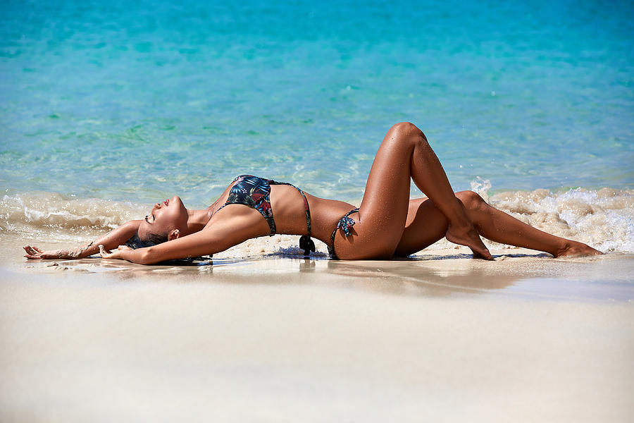 Sexy woman wearing designer bathing suits while in the sand