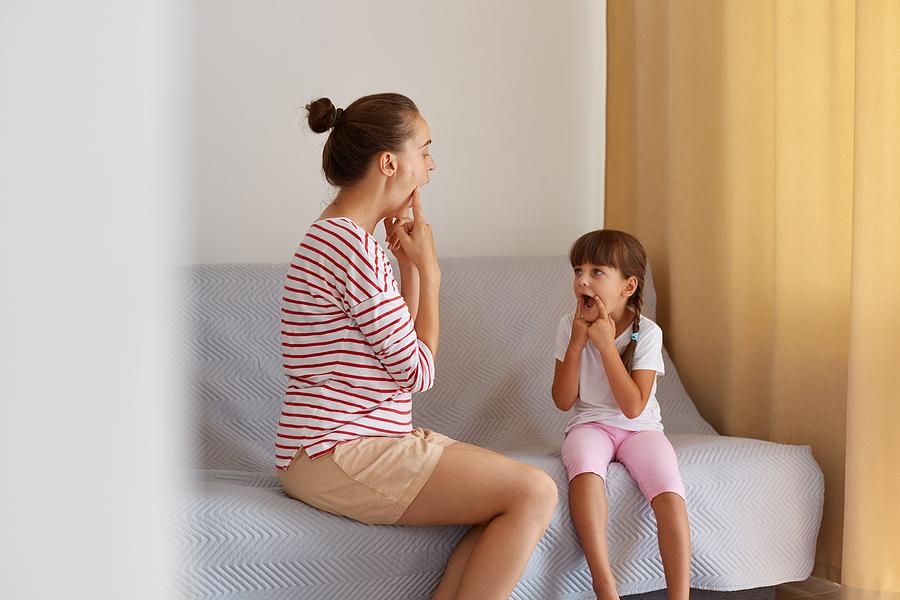 Speech therapist helping a little girl with speech difficulty